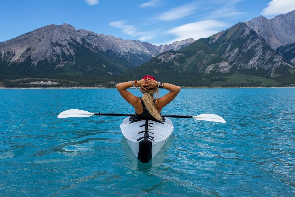 A woman in a kayak. The water is bright blue, and she is admiring the mountains in front of her.