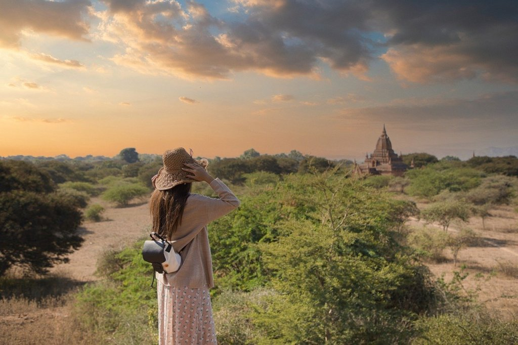 A woman is looking at a temple in Myanmar from afar. She is in a field, wearing a sunhat, beige cardigan and long skirt.