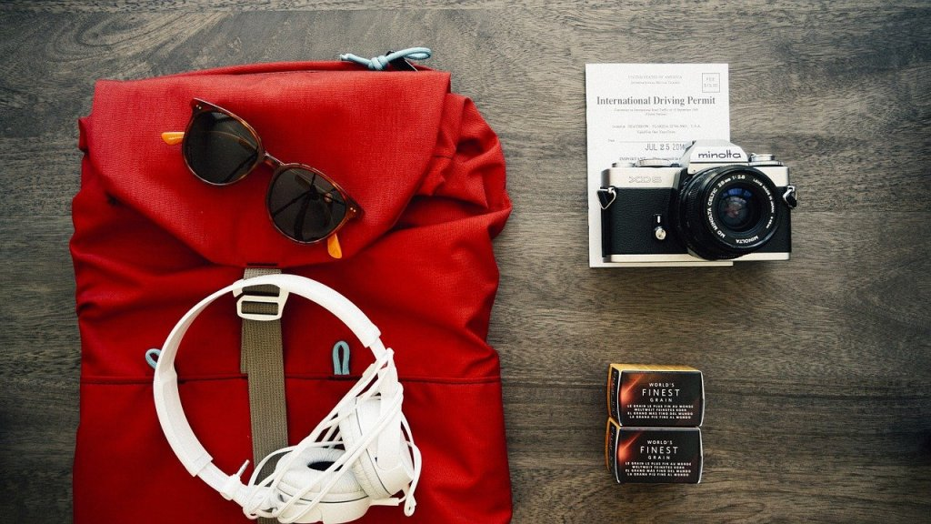 A backpack laid flat on a wooden surface. On top of it is a pair of white over-ear headphones and sunglasses. Next to it is a camera and international driving permit.