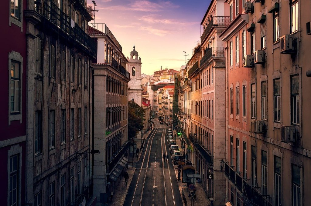 A narrow street in Lisbon at sunset.