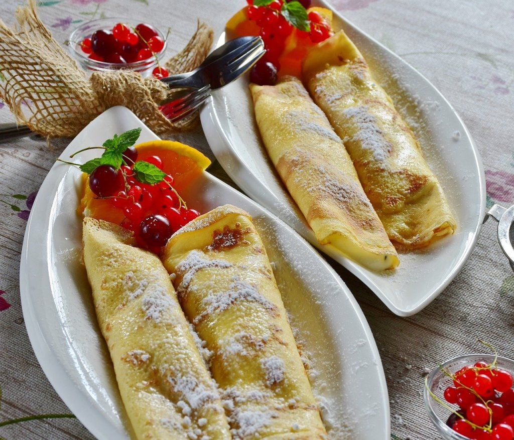 Two long oval shaped plates, each one containing two rolled up crepes. Freshly cut orange and pomegranate is at the end of each plate.
