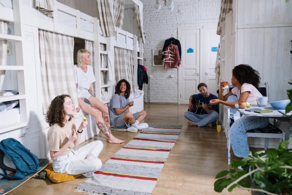 Group of people sitting on a hostel floor in their pyjamas.