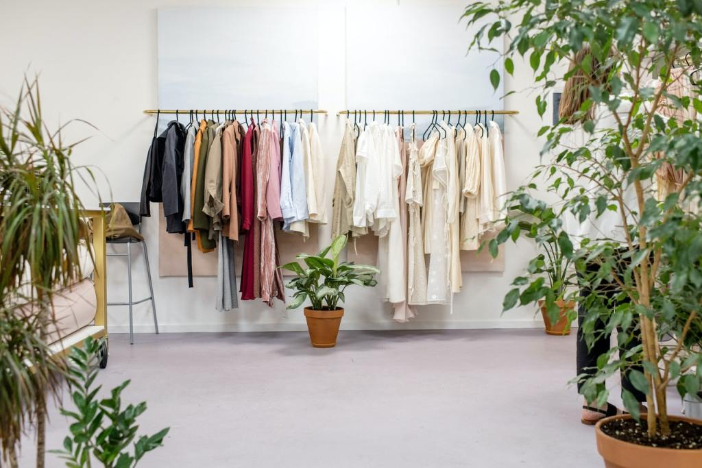Clothes hanging on a clothes rack in a white room. Potted plants are dotted throughout the room.