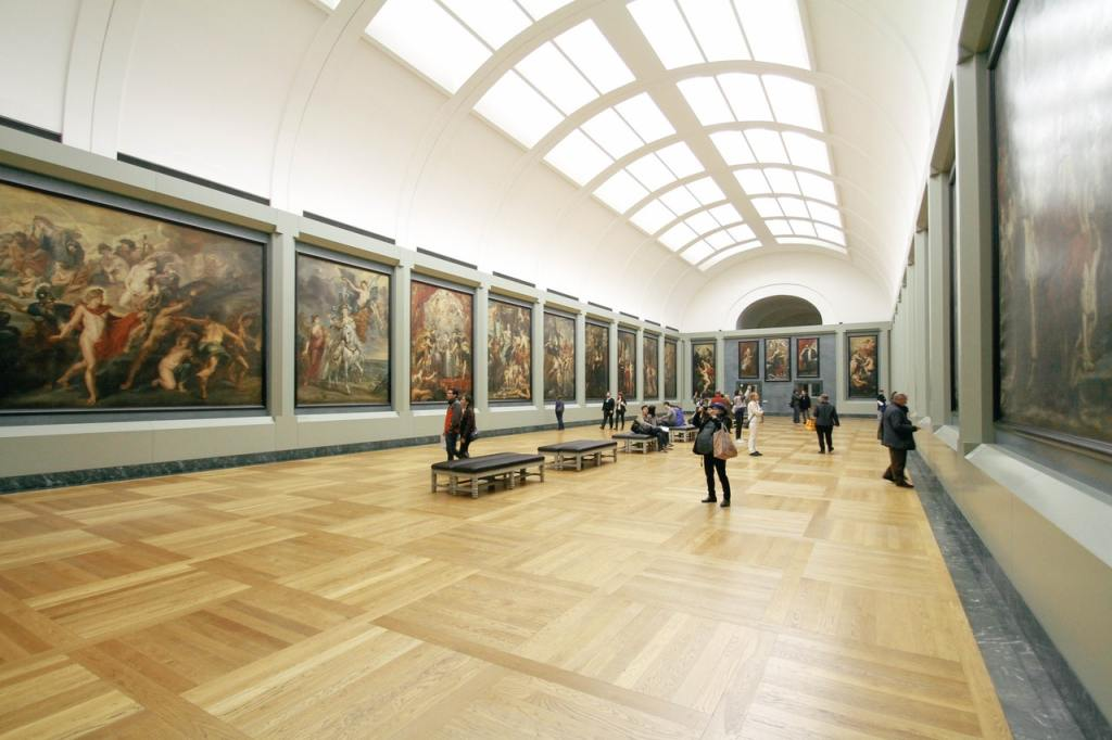 A long and narrow room in an art gallery. Artwork is hanging from the walls and the room is filled with natural light from ceiling windows.