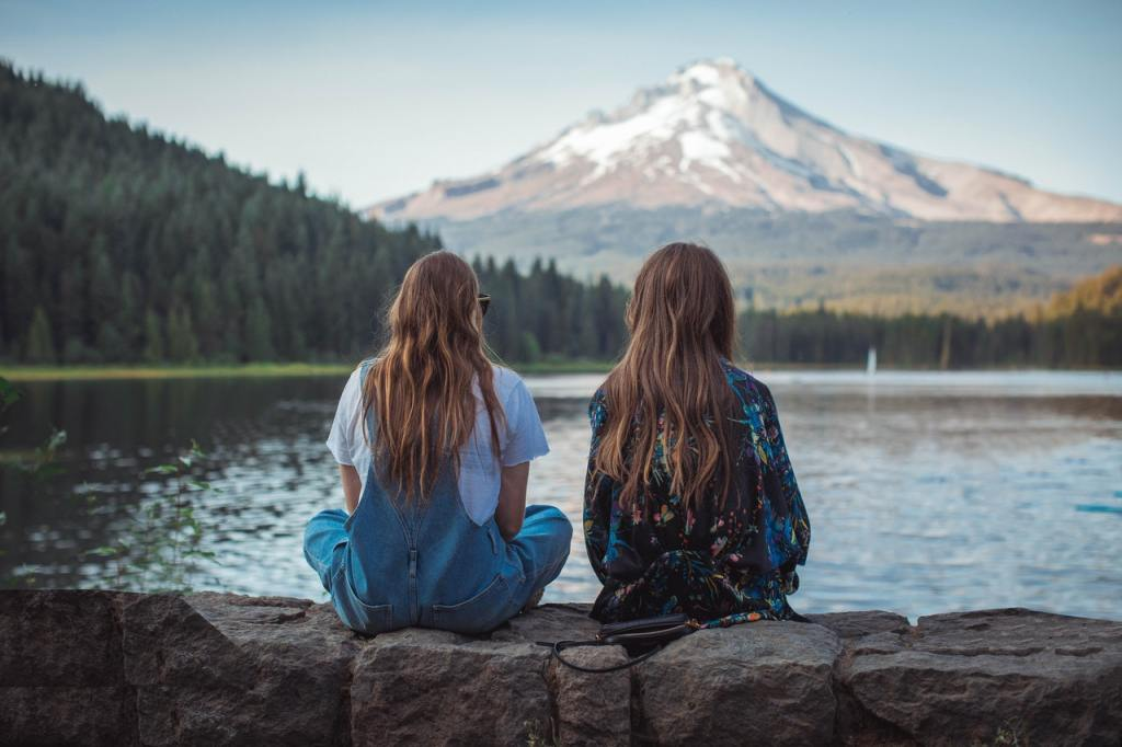 Two women sitting on a rock facing a body of water and a mountain.