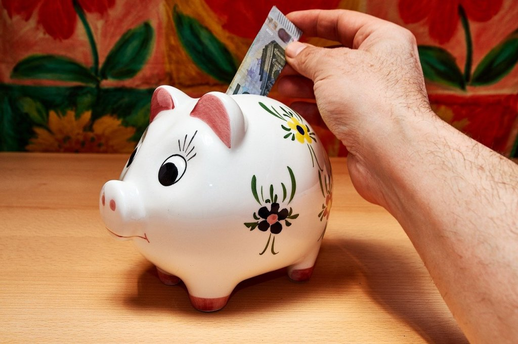 Someone putting a note into a piggy bank.