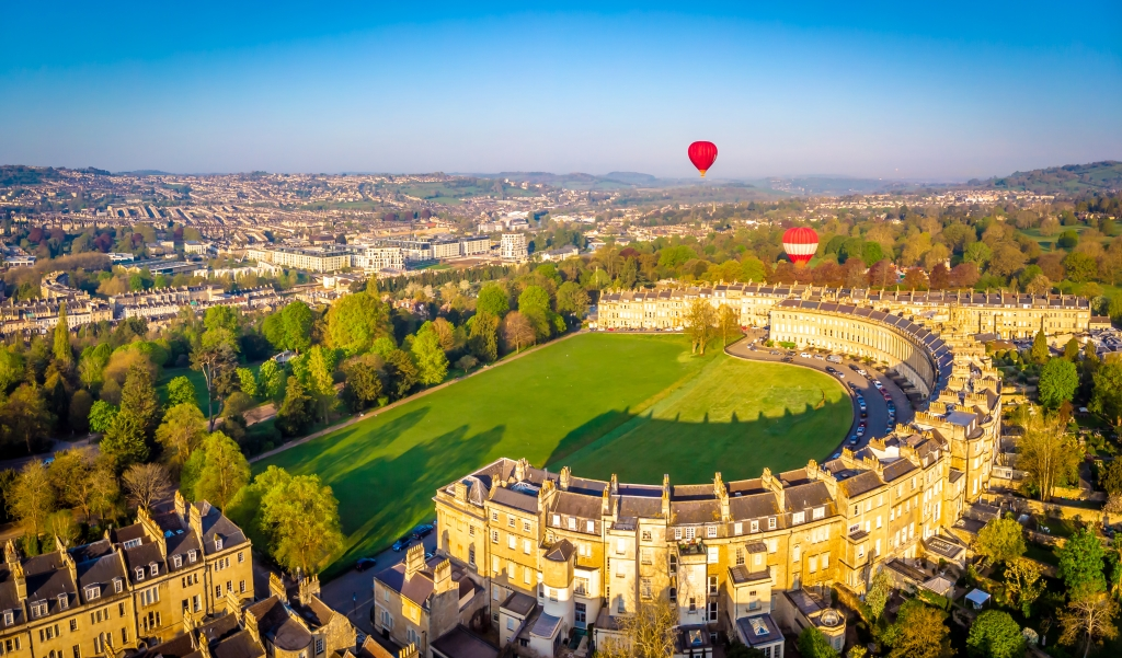 A drone shot of Bath crescent on a sunny day. Two hot air balloons are floating in the sky.
