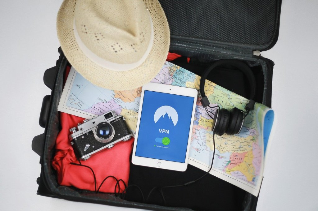 An open suitcase, containing a map, headphones, a camera, a sunset and a smart phone.