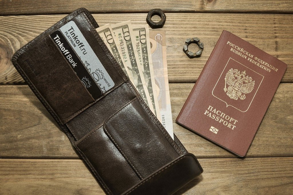 A passport and wallet on a wooden table. The wallet is open, and four notes are sticking out.