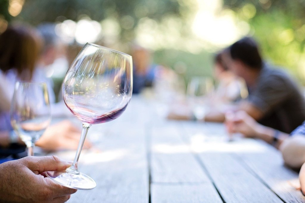 A hand holding an almost empty glass of wine, on a long wooden table.