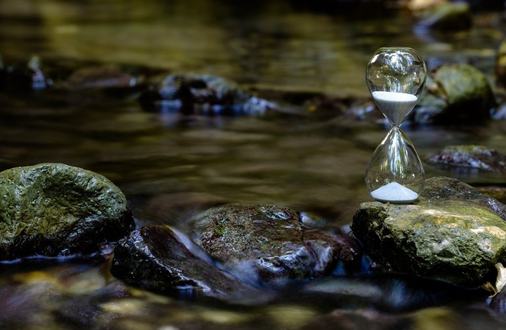 An hourglass rests on a stone in a shallow river.
